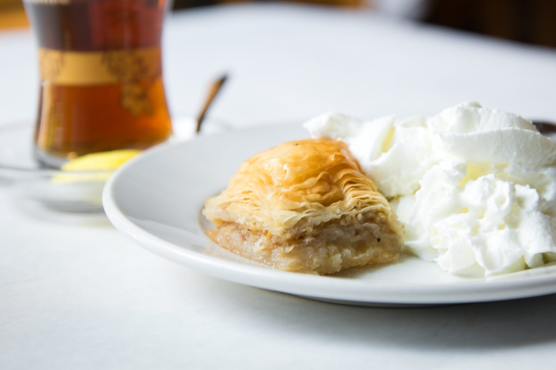 Homemade Baklava with a drizzle of honey and whipped cream, perfect with a glass of Turkish tea.